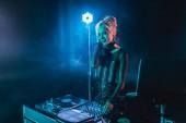 happy blonde dj girl in headphones standing near dj mixer in nightclub with smoke