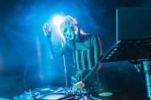 Fotografie smiling blonde dj girl in headphones standing near dj mixer in nightclub with smoke