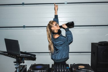 dj woman in glasses gesturing near dj mixer and drinking wine from bottle
