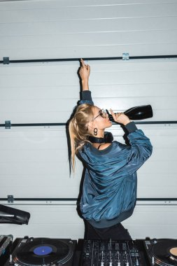 dj woman gesturing near dj mixer and drinking wine from bottle