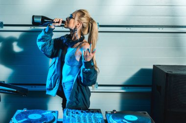 dj woman gesturing near dj mixer while drinking wine from bottle
