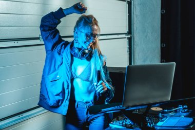 attractive and stylish dj woman in glasses dancing near laptop