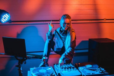 cheerful stylish dj woman in glasses gesturing while touching dj mixer