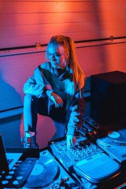stylish dj woman in glasses touching dj mixer in nightclub
