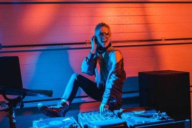 Cheerful dj girl in glasses touching dj mixer in nightclub stock vector