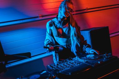 attractive blonde dj woman holding bottle while touching vinyl record