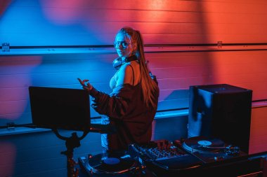 Beautiful blonde dj woman gesturing while standing in nightclub stock vector