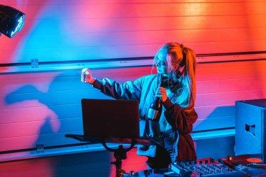 attractive blonde dj woman holding bottle and taking selfie in nightclub