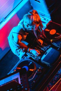 overhead view of blonde dj girl touching dj mixer in nightclub