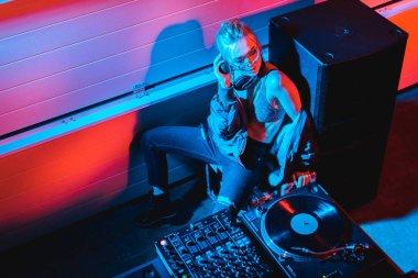 Overhead view of dj girl with blonde hair sitting near dj equipment in nightclub stock vector