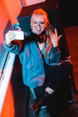 cheerful dj woman in glasses taking selfie while gesturing in nightclub