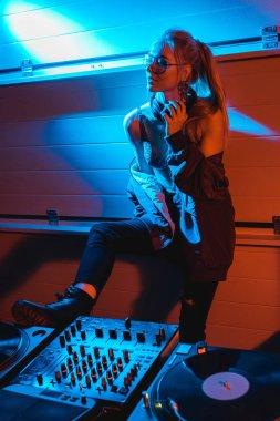attractive blonde dj girl in glasses standing and touching headphones in nightclub