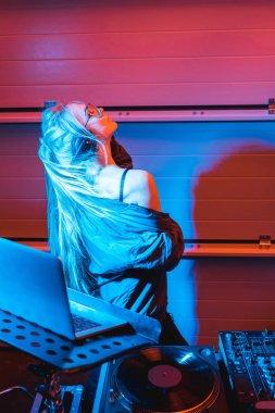 dj woman in headphones standing near laptop in nightclub