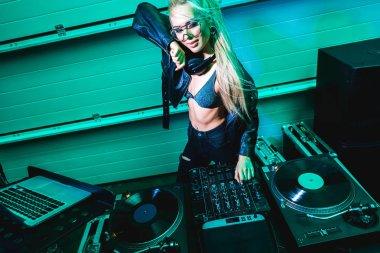 happy blonde dj girl in glasses touching dj mixer in nightclub