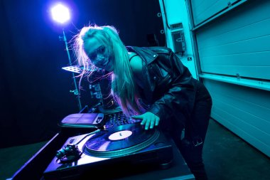 happy dj girl touching vinyl record in nightclub