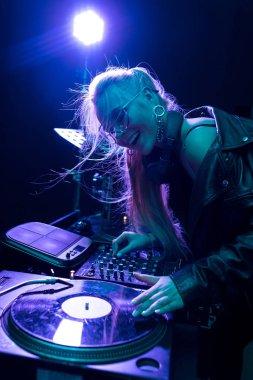 happy blonde dj girl touching vinyl record and smiling in nightclub