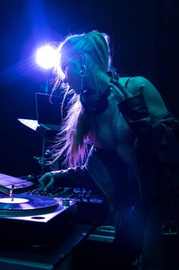 blonde stylish dj girl touching dj mixer in nightclub