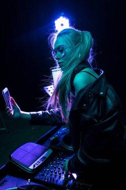 stylish dj girl touching dj equipment while taking selfie in nightclub