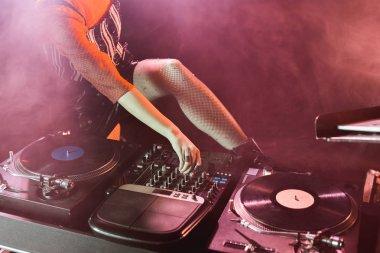cropped view of dj girl touching dj mixer in nightclub with smoke