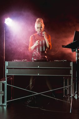 attractive and stylish dj girl in headphones looking at dj mixer in nightclub with smoke