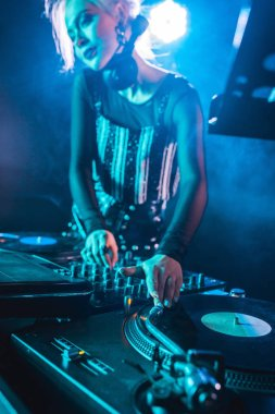 selective focus of blonde dj girl standing near dj mixer and touching vinyl records in nightclub with smoke