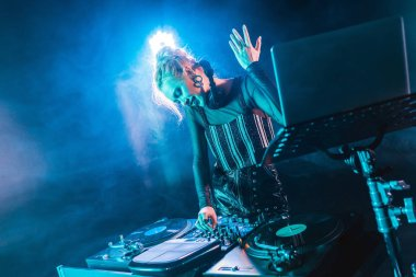 smiling blonde dj girl in headphones standing near dj mixer and gesturing in nightclub with smoke