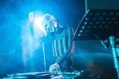 Fotografie selective focus of happy dj girl in headphones standing near dj mixer in nightclub with smoke