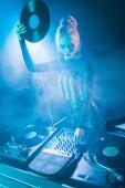szőke dj lány keresi dj felszerelés és a gazdaság retro bakelit, nightclub, füst