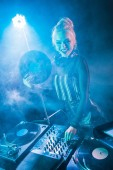 smiling blonde dj girl touching dj equipment and holding retro vinyl record in nightclub with smoke