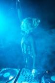 happy blonde dj woman in headphones holding  bottle near dj equipment in nightclub with smoke