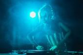 Fotografie beautiful dj girl in headphones using dj equipment in nightclub with smoke