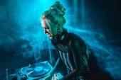 angry blonde dj girl using dj equipment in nightclub with smoke