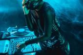 cropped view of dj woman using dj mixer in nightclub with smoke