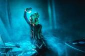 Happy dj žena s blond vlasy poslech hudby ve sluchátkách v nočním klubu s kouřem