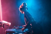 dj woman with blonde hair using dj mixer and touching vinyl record in nightclub with smoke