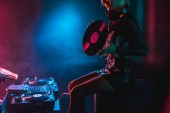 cropped view of smiling dj woman holding retro vinyl record in nightclub with smoke