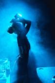 silhouette of dj woman standing in nightclub with smoke
