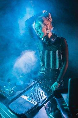 Happy blonde dj girl in headphones standing near dj equipment in nightclub with smoke stock vector
