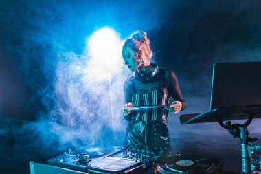 attractive dj woman looking at dj equipment and holding retro vinyl record in nightclub with smoke