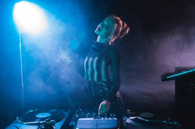 blonde dj woman standing with closed eyes near dj equipment and holding retro vinyl record in nightclub with smoke