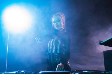 blonde dj woman holding retro vinyl record and looking at dj equipment in nightclub with smoke