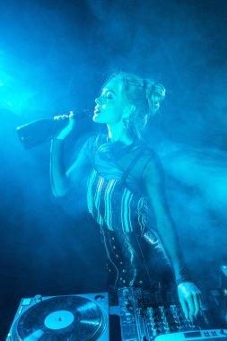 blonde dj woman in headphones drinking wine from  bottle near dj equipment in nightclub with smoke