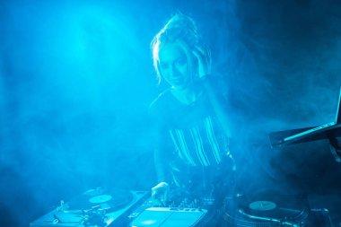 cheerful blonde dj girl listening music in headphones near dj equipment in nightclub with smoke