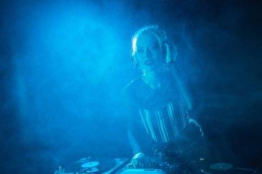attractive dj girl listening music in headphones near dj equipment in nightclub with smoke