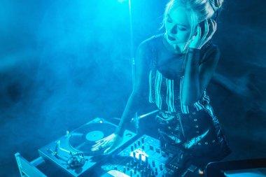 blonde dj girl listening music in headphones while looking at dj equipment in nightclub with smoke