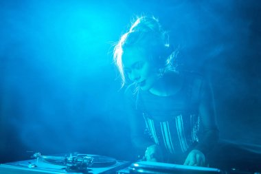happy blonde dj girl listening music in headphones while using dj equipment in nightclub with smoke
