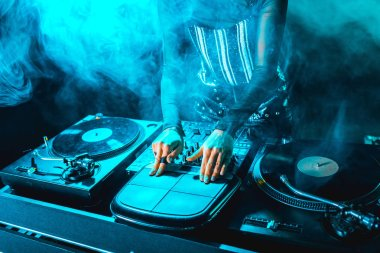 cropped view of dj woman using dj equipment in nightclub with smoke