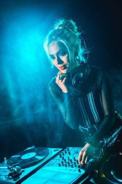 beautiful blonde dj girl using dj equipment in nightclub with smoke