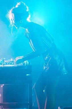 beautiful dj woman with blonde hair using dj mixer in nightclub with smoke