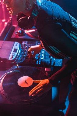 cropped view of focused dj woman using dj equipment in nightclub